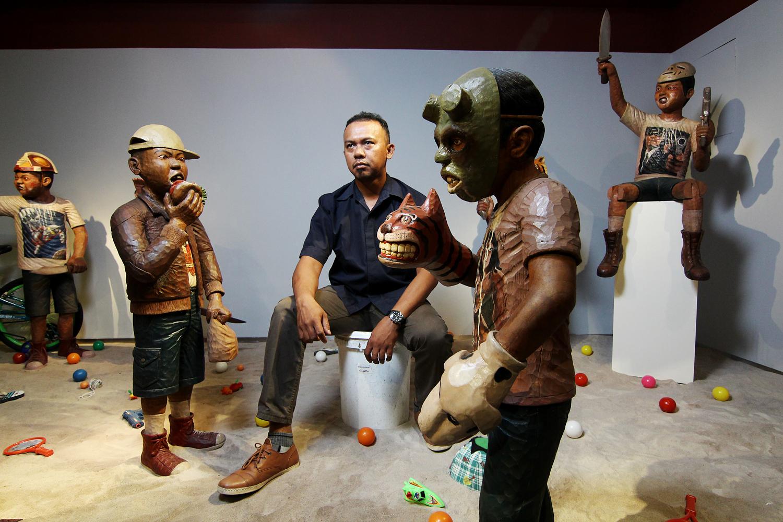 Abdi Setiawan diantara karya-karyanya yang tampil perdana di Rebbase Art Gallery, Ciputra World 1, Jakarta.