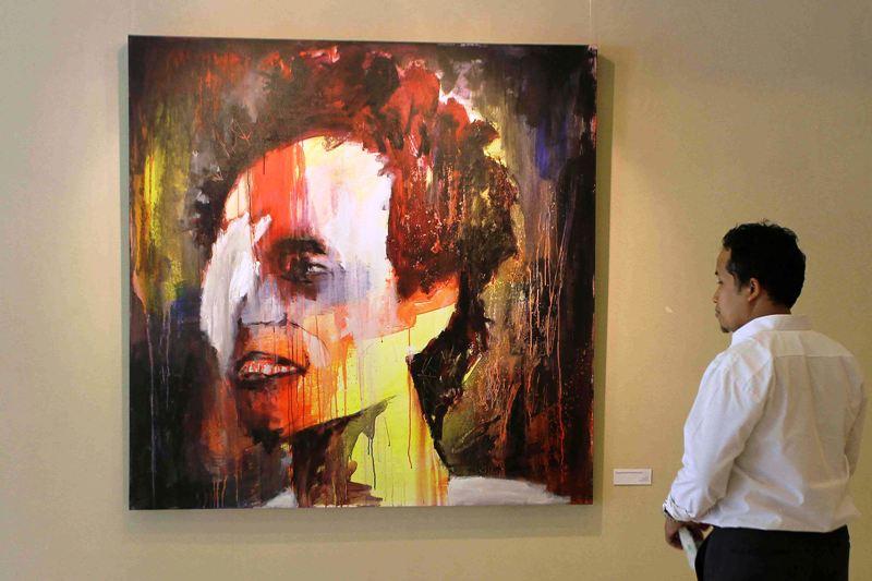 Seorang pengnjung tengah memperhatikan karya lukis Patrick Wowor yang dipamerkan di pameran tunggalnya bertema Underexposed di Galeri 3, Taman Ismail Marzuki - Jakarta.