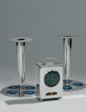 Sepasang tempat lilin dan jam meja yang didesain oleh Archibald Knox (Inggris, 1864-1933).