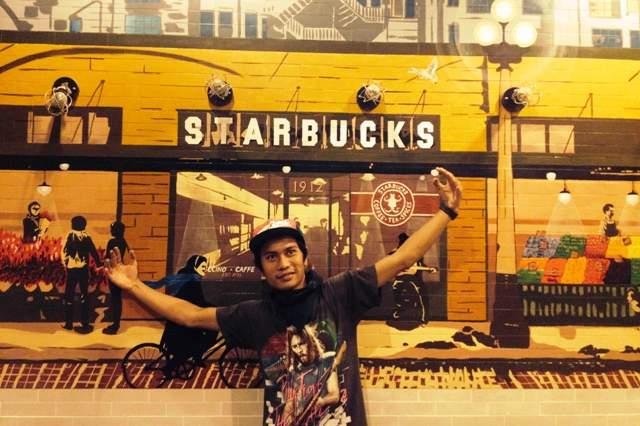 Gigin Ginanjar di depan salah satu desain muralnya di gerai Starbucks Indonesia.